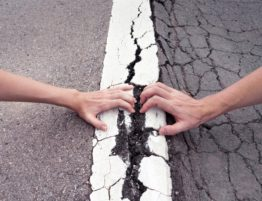 hands pulling on street crack