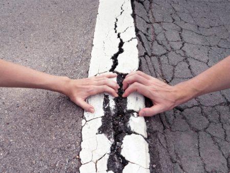 hands pulling on street crack