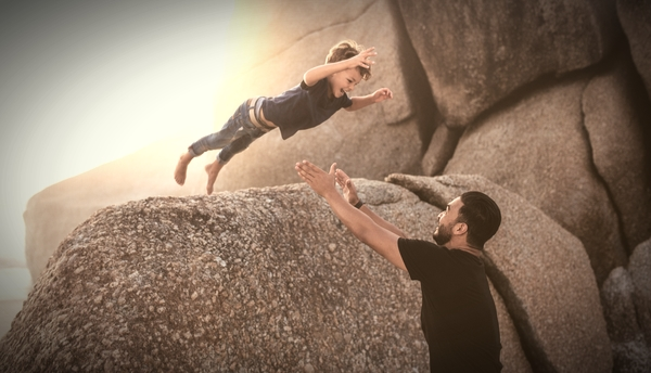 Young boy jumping off rock into fathers arms